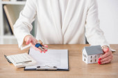 partial view of businesswoman at workplace holding keys and touching house model near clipboard and calculator