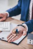 részleges kilátás üzletember a munkahelyen mutatja kulcsok közelében ház modell, írótábla és számológép