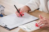 oříznutý pohled na podnikatelku pomocí kalkulačky a psaní ve smlouvě v blízkosti domu model a klíče