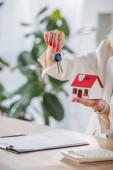 Teilansicht einer Geschäftsfrau, die Hausmodell und Schlüssel in der Nähe von Klemmbrett und Taschenrechner zeigt