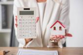 částečný pohled na podnikatelku ukazující model domu a kalkulačku