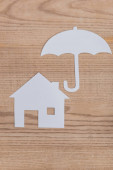 Fotografie top view of white paper cut house and umbrella on wooden desk