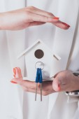 partial view of businesswoman holding and covering house model and keys with hand