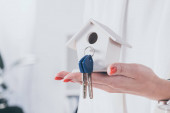 partial view of businesswoman holding house model with keys