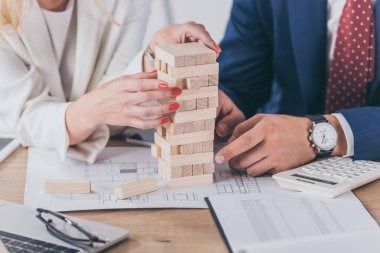 cropped view of risk managers sitting at workplace near stacked wooden blocks