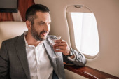 handsome businessman holding martini glass with drink in private jet