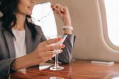 oříznutý pohled na podnikatelku držící Martini sklo v soukromém tryskáči