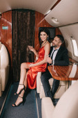 selective focus of happy couple holding martini glasses in private jet