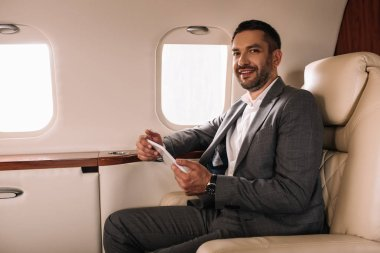 Cheerful bearded businessman in suit using smartphone in private jet stock vector