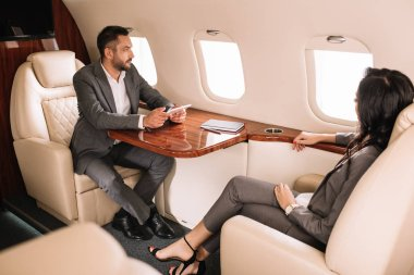Selective focus of handsome bearded businessman holding gadget while sitting with businesswoman in private jet stock vector