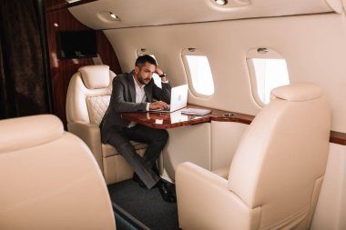 Selective focus of bearded businessman using laptop in private jet stock vector