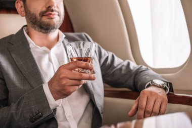 Cropped view of bearded man holding glass with whiskey in private jet stock vector