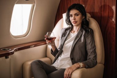 Businesswoman holding glass with cognac in private jet stock vector