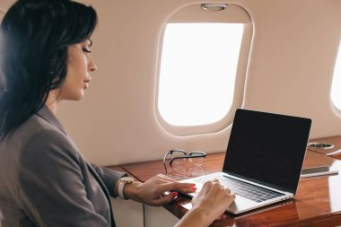 Selective focus of attractive businesswoman using laptop with blank screen in private jet stock vector