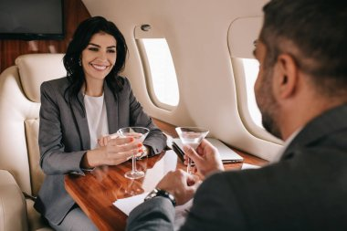 Selective focus of happy businesswoman and bearded businessman holding martini glasses in private jet stock vector