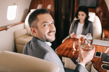 Selective focus of happy businessman holding jar with alcohol drink near businesswoman in private jet stock vector