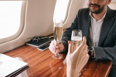 Cropped view of woman and bearded man holding champagne glasses in private jet stock vector