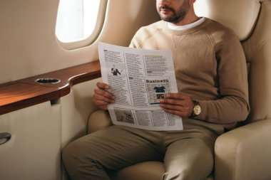 Cropped view of bearded man holding newspaper in private jet stock vector