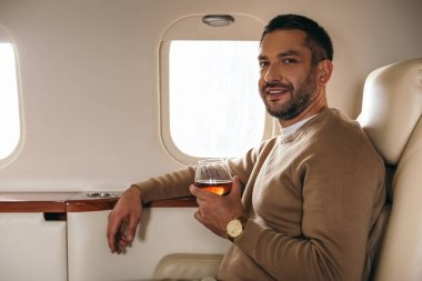 Cheerful man holding glass with cognac while sitting in first class of private jet stock vector