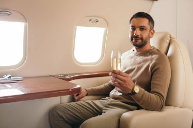 Cheerful man holding champagne glass while sitting in first class of private jet stock vector