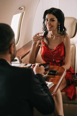 Selective focus of elegant woman in red dress holding martini glass and looking at man in private jet stock vector