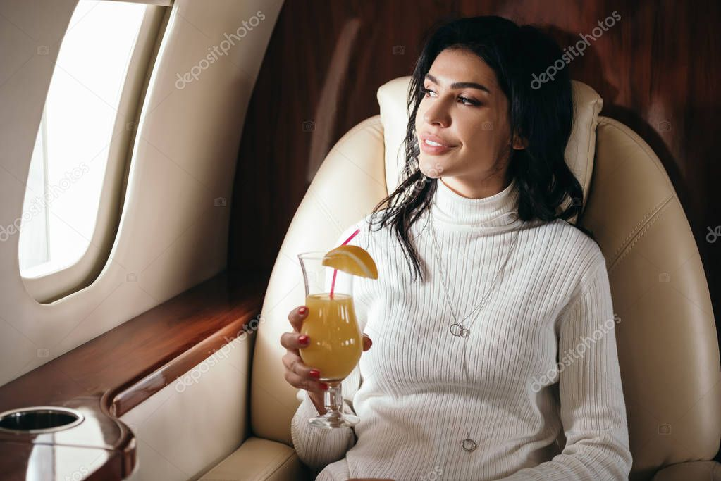 Happy woman holding tasty cocktail in private jet stock vector