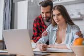 selektivní zaměření usměvavý muž dotýkání ramen hezké přítelkyně pracující na notebooku