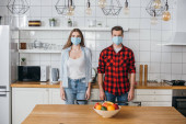 Photo young couple in medical masks looking at camera while standing in modern kitchen