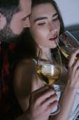 junger Mann umarmt verträumte Freundin, während er mit Weißweingläsern auf dem Sofa sitzt