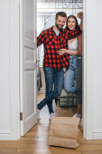happy young couple smiling at camera while opening door near paper bag with delivered food