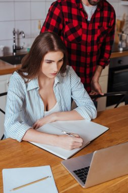 cropped view of man standing near serious girlfriend looking at laptop and writing in notebook