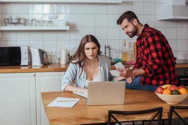handsome man holding smartphone while sitting on table near serious girlfriend working on laptop