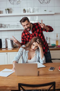 cheerful man fooling around near exhausted girlfriend sitting near laptop and notebook in kitchen