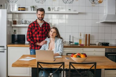 attractive freelancer sitting at table near laptop while smiling boyfriend touching her shoulders in kitchen