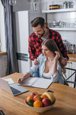 handsome man touching shoulders of attractive girlfriend looking at laptop and writing in notebook in kitchen