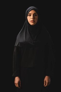 Beautiful muslim woman in hijab looking at camera isolated on black