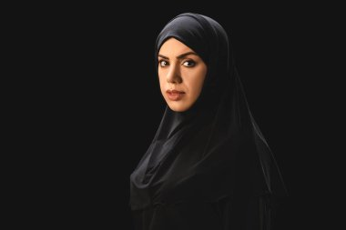 Side view of beautiful muslim woman looking at camera isolated on black