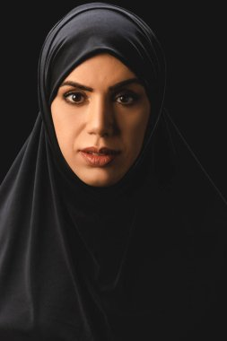 Portrait of beautiful muslim woman in traditional hijab looking at camera isolated on black