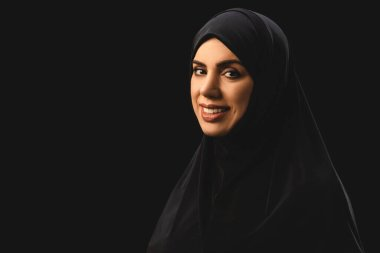 Beautiful muslim woman in hijab smiling at camera isolated on black