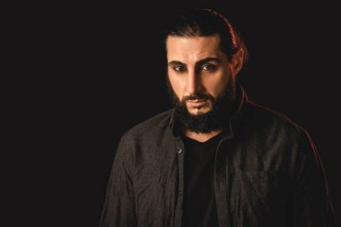 Handsome bearded muslim man looking at camera isolated on black