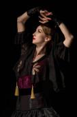 schöne Tänzerin mit Händen über dem Kopf tanzt Flamenco isoliert auf schwarz