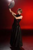 Photo pretty flamenco dancer in dress holding fan above head on red