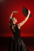 Photo young flamenco dancer in dress looking at fan on red