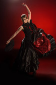 Photo pretty flamenco dancer in dress holding fan while dancing on red
