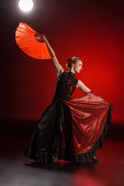 Photo elegant flamenco dancer touching dress and holding fan while dancing on red
