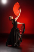 Photo young woman in dress holding fan while dancing flamenco on red