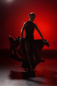 Photo silhouette of young woman touching dress and dancing flamenco on red