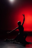 Photo silhouette of young flamenco dancer in dress dancing on red
