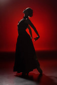 Photo silhouette of elegant young woman dancing flamenco on red