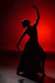 Photo silhouette of elegant girl dancing flamenco on red